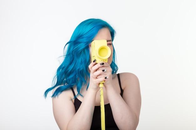 Красивая женщина с синими волосами держит желтый ретро фотоаппарат на белой стене
