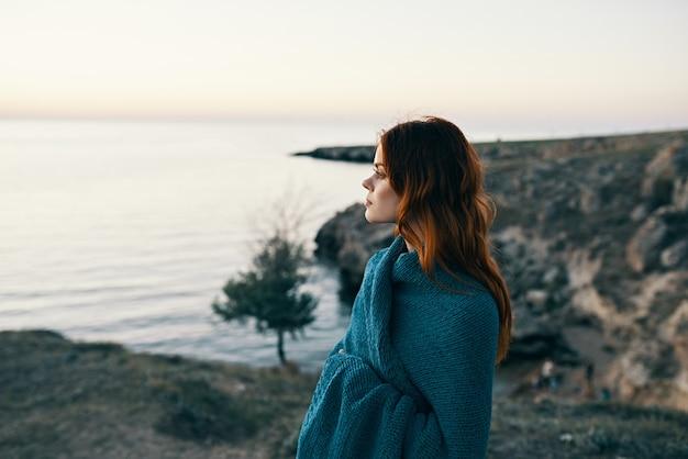 青い格子縞と赤い髪の山の風景と美しい女性