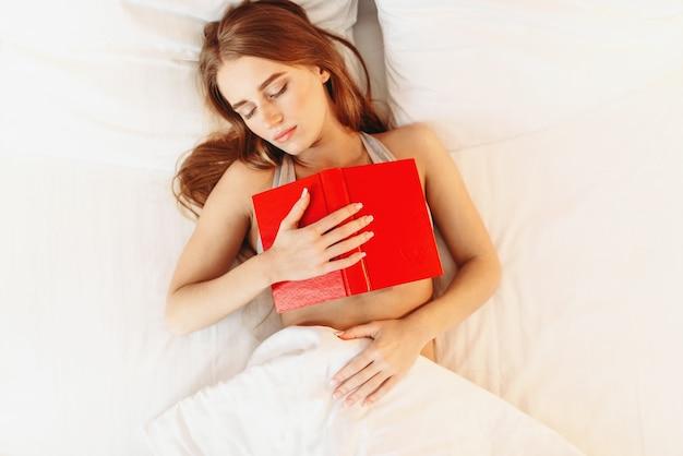 Красивая женщина с книгой, спать в постели, вид сверху. девушка заснула во время чтения в спальне