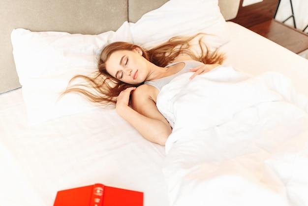 Красивая женщина с книгой, спящей в постели