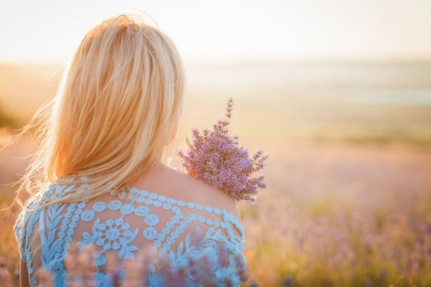 Beautiful woman with a bouquet of lavender enjoying the sunset