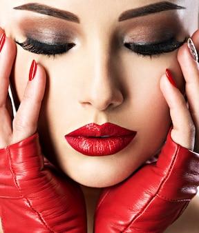 明るいファッションメイクとセクシーな唇に赤い口紅を持つ美しい女性。クローズアップの肖像画。