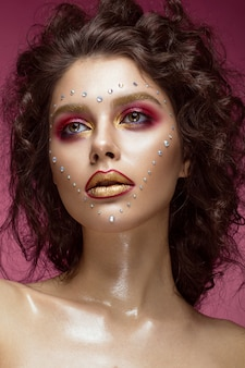 Beautiful woman with bright fashion make-up, and heart from crystals on the face