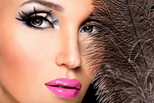 Beautiful woman with bright professional make-up with feathers near the face.
