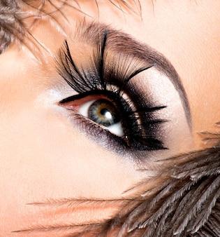 顔の近くに羽を持つ明るいプロのメイクアップの美しい女性。