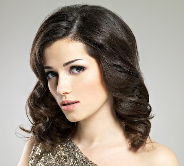 茶色の巻き毛のポーズの美しい女性