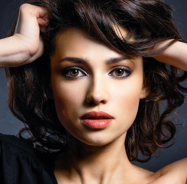 茶色の髪の美しい女性。茶色の目を持つ魅力的なモデル。スモーキーメイクのファッションモデル。きれいな女性のクローズアップの肖像画。クリエイティブなヘアスタイル。