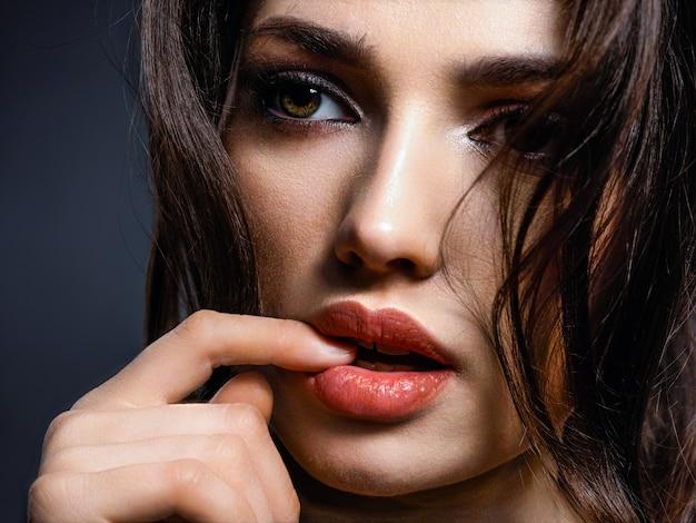 갈색 머리를 가진 아름 다운 여자입니다. 갈색 눈을 가진 매력적인 모델. 스모키 메이크업 패션 모델. 예쁜 여자의 근접 촬영 초상화는 카메라를 살펴 봅니다.