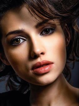 茶色の髪の美しい女性。茶色の目を持つ魅力的なモデル。スモーキーメイクのファッションモデル。きれいな女性のクローズアップの肖像画。