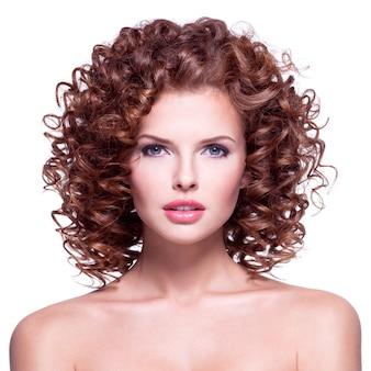 Красивая женщина с вьющимися волосами брюнет - изолированная на белой предпосылке.