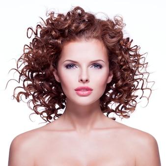 Красивая женщина с вьющимися волосами брюнет - изолированная на белой стене.
