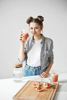 Красивая женщина с плюшками, улыбаясь, пить грейпфрут детокс коктейль на белой стене. здоровое питание