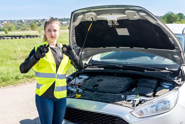 Beautiful woman with car filters on roadside