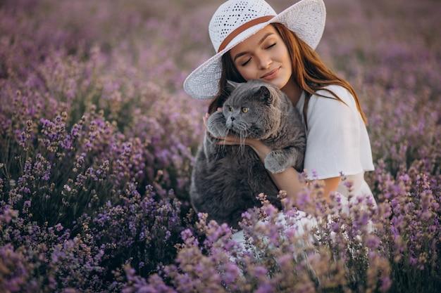 Красивая женщина с кошкой в поле лаванды