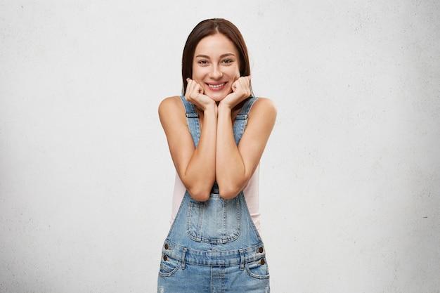 Bella donna con un sorriso affascinante con un'espressione gioiosa sul viso, tenendosi per mano sul viso, compiaciuta di un complimento o di un bel regalo.