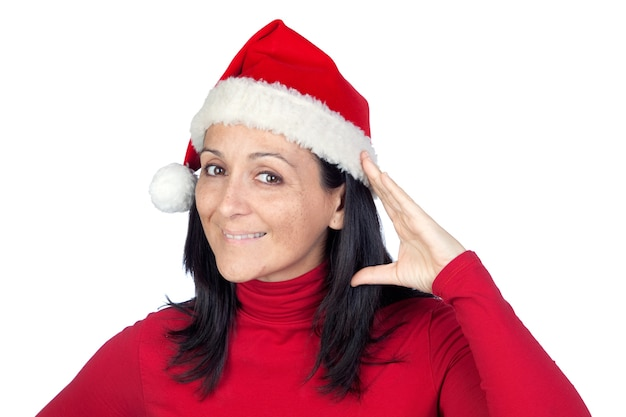 Beautiful woman with christmas hat making the gesture of listening on a over white background