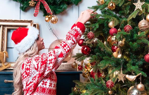 コーンと雪の結晶とライトと新年の装飾ボールとクリスマススプルースモミの花輪を持つ美しい女性。