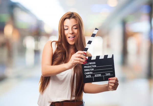 Beautiful woman with clapper board in shopping centre