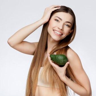 Красивая женщина с чистой свежей кожей, холдинг авокадо