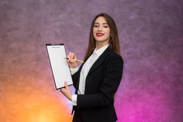 Beautiful woman with clipboard offering sign a contract with pen