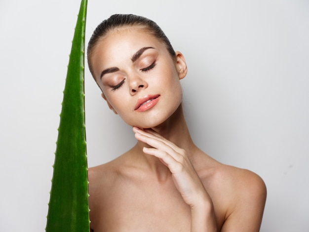 Beautiful woman with closed eyes and green aloe leaf on light background