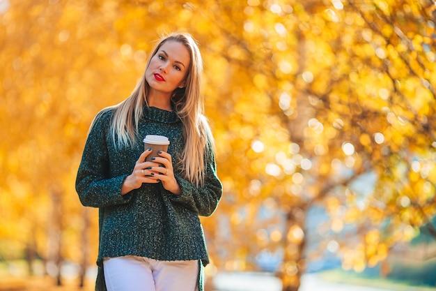 Красивая женщина с кофе в осеннем парке под осенней листвой в теплый день