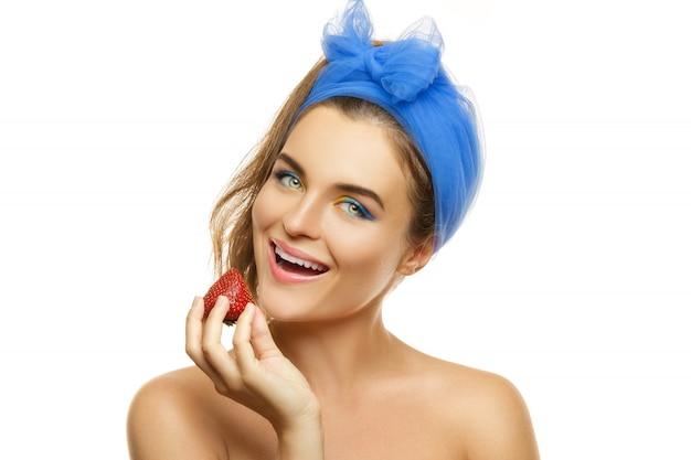 カラフルなメイクアップとイチゴの美しい女性
