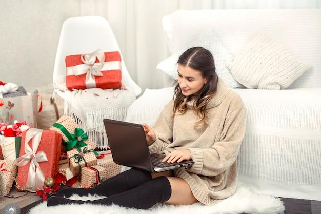 コンピューターとクリスマスプレゼントの美しい女性。