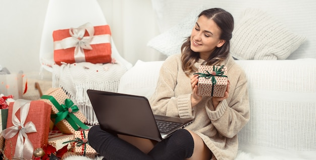 Красивая женщина с компьютером и рождественскими подарками.