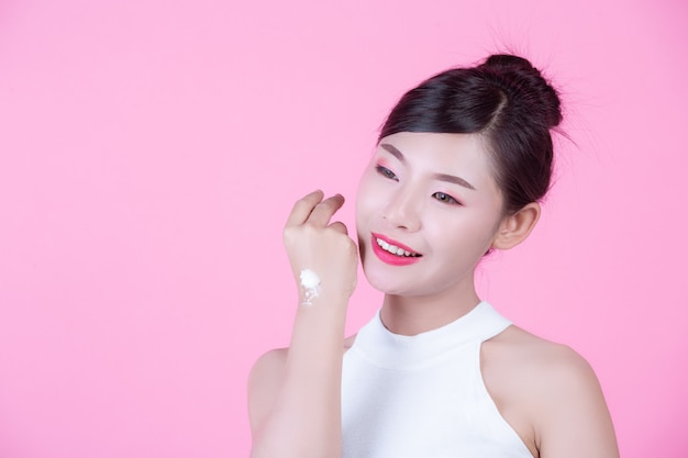 Beautiful woman with cream on the skin on a pink background.