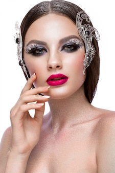 Beautiful woman with creative art make-up and silver accessories