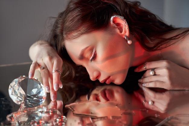 創造的なメイクの美しい女性が鏡に横たわっています