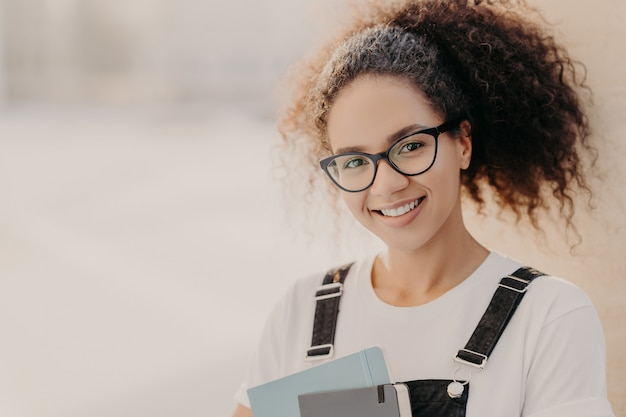 Beautiful woman with crisp hair combed in pony tail, carries notepad, wears white t shirt and overalls