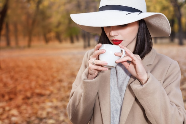 Beautiful woman with cup of coffee in the autumn park