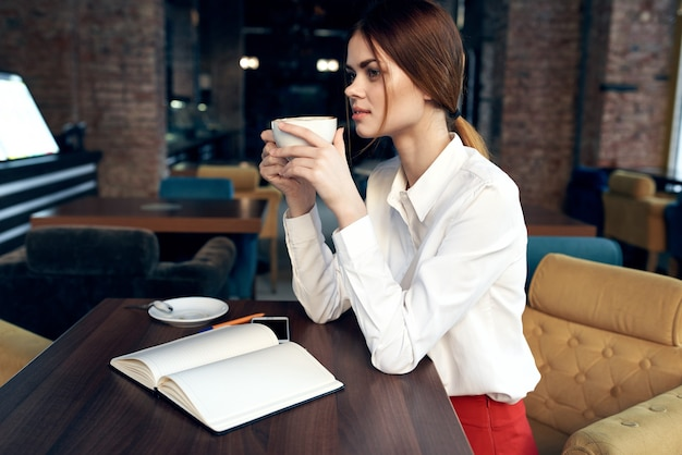 Beautiful woman with a cup in hand sits at a table in a cafe and book a restaurant