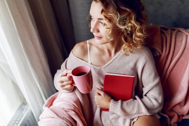 Красивая женщина с чашкой кофе и чтением