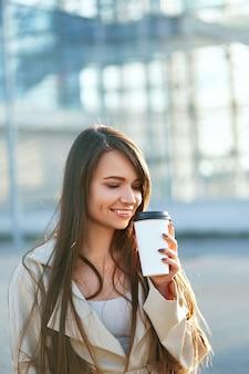 거리에 걷는 커피 한잔과 함께 아름 다운 여자. 야외 서 뜨거운 음료 컵을 들고 세련된 사무실 옷에 매력적인 젊은 여성의 초상화