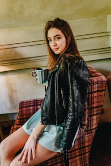 Beautiful woman with cup of tea or coffee. girl drinking coffee in a cafe. brunette, coffee