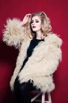 Красивая женщина с вьющимися светлыми волосами на ярко-красном фоне