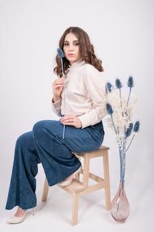 青いズボンと肘掛け椅子に座っているベージュの青銅の巻き毛の茶色の髪を持つ美しい女性