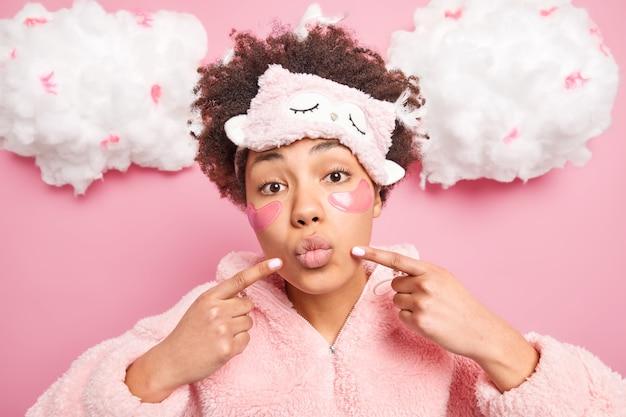唇の角に巻き毛のふさふさした髪のポイントを持つ美しい女性は、新鮮な肌が目の下にコラーゲンパッチを適用して、屋内で柔らかい眠りのスーツのポーズに身を包んだ細い線を減らします
