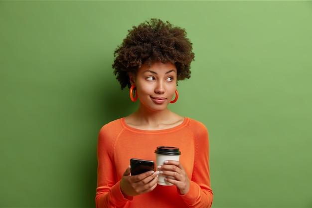 巻き毛の美しい女性はおいしいコーヒーの紙コップを保持し、スマートフォンは鮮やかな緑の壁に隔離されたカジュアルなオレンジ色のセーターを着てメッセージを送信します