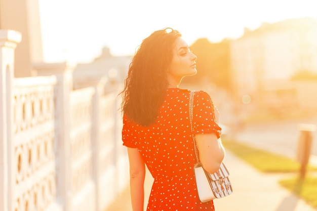 패션 핸드백과 빈티지 빨간 드레스에 곱슬 머리를 가진 아름 다운 여자는 일몰에 도시에서 산책