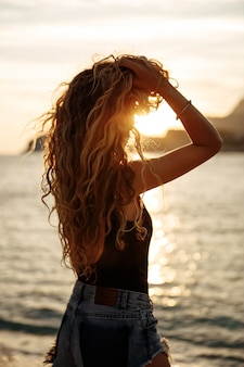 Beautiful woman with curly hair near the sea