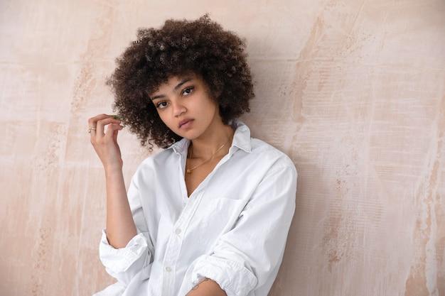 Bella donna con i capelli ricci in posa