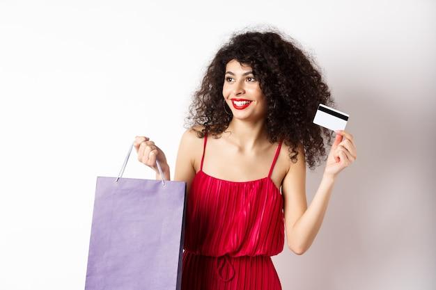 巻き毛、赤いドレス、ショッピングバッグとプラスチックのクレジットカード、白い背景を示す美しい女性。