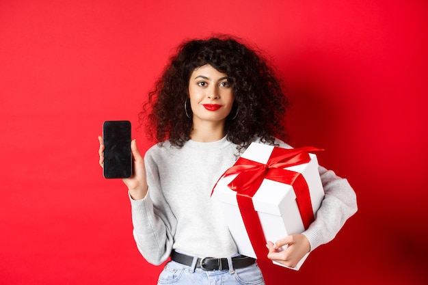 Beautiful woman with curly hair, showing shopping app on empty smartphone screen, holding gift wrapped in festive box, standing on red wall.