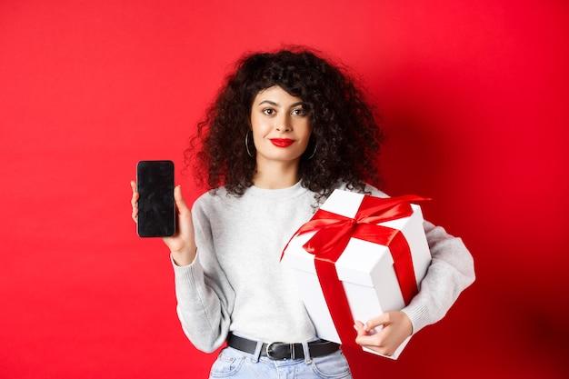 곱슬 머리를 가진 아름 다운 여자, 빈 스마트 폰 화면에 쇼핑 앱을 보여주는 빨간색 배경에 서있는 축제 상자에 싸여 선물을 들고.