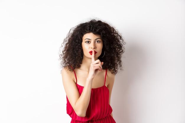 Красивая женщина с вьющимися волосами, в красном платье, замолкает в камеру, рассказывает секрет, шепчет вам, стоя на белом фоне.