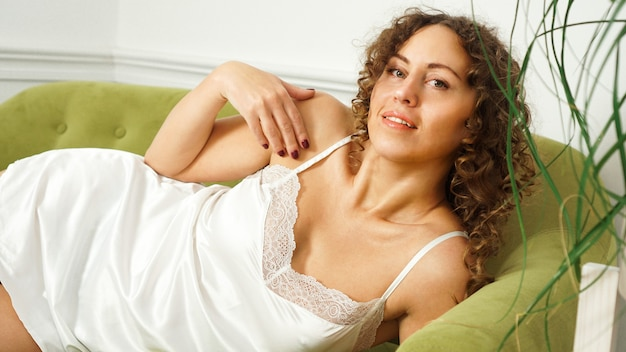 Beautiful woman with curly hair in white lingerie sitting on green sofa at home - happy morning